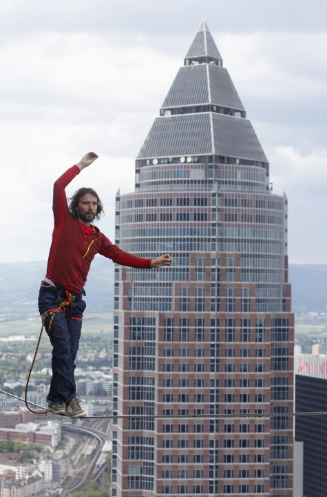 Professional slackliner Reinhard Kleindl walks a high wire in front of  the Messeturm Fair Tower in Frankfurt