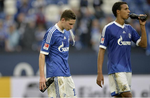 Schalke's Julian Draxler, left, reacts after losing the German  Bundesliga  soccer match between FC Schalke 04 and Borussia Dortmund in Gelsenkirchen, Germany, Saturday, Oct. 26, 2013