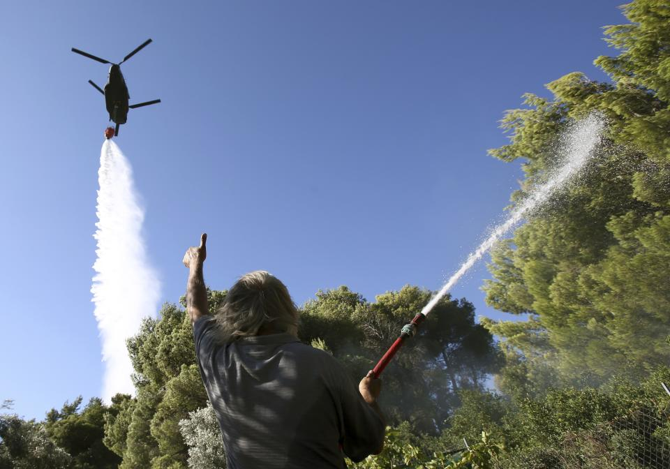 A local resident gestures to a military helicopter dropping water over a burning forest in Varibobi, a northwestern suburb of Athens, Tuesday, Aug. 6, 2013. A large wildfire raged through the suburb burning about four homes. No injuries were reported. (AP Photo/Thanassis Stavrakis)