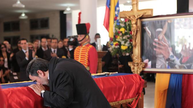 In this photo released by Miraflores Press Office, Iran's President Mahmoud Ahmadinejad kisses the flag-draped coffin of late Venezuela's President Hugo Chavez during the funeral ceremony at the military academy in Caracas, Venezuela, Friday, March 8, 2013. Chavez died on March 5 after a nearly two-year bout with cancer.  He was 58.  (AP Photo/Miraflores Press Office)