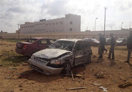 Men stand next to a car damaged after an explosion in the eastern city of Benghazi
