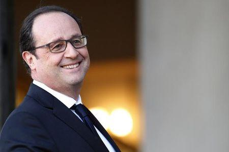 French President Francois Hollande walks back to his office after a meeting with a guest at the Elysee Palace in Paris