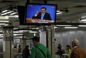 Passengers walk past a TV showing a live broadcasting…