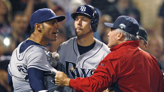 Boston Red Sox pitching coach Bob McClure, right, grabs the jersey of Tampa Bay Rays' Carlos Pena, left, as benches cleared after Rays designated hitter Luke Scott was hit by a pitch during the ninth inning of a baseball game at Fenway Park in Boston, Friday, May 25, 2012.  At center is Rays' Ben Zobrist. (AP Photo/Charles Krupa)
