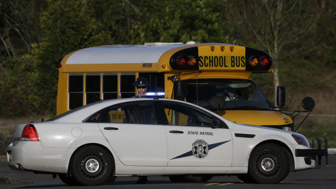 A school bus turns around after encountering a Washington State Patrol trooper staffing a roadblock about a block from the scene of an overnight shooting that left five people dead, Monday, April 22, 2013, at an apartment complex in Federal Way, Wash. (AP Photo/Ted S. Warren)
