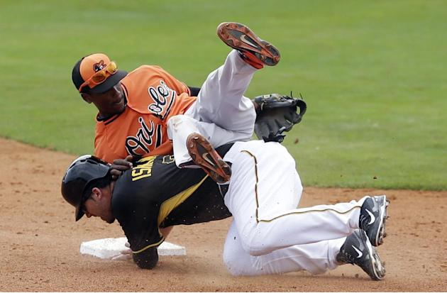 Baltimore Orioles second baseman Jemile Weeks, top, falls over Pittsburgh Pirates' Travis Ishikawa after throwing to first during the fifth inning of a spring exhibition baseball game in Bradenton