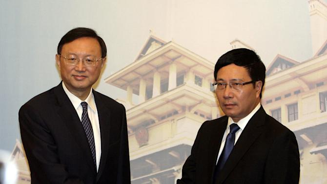Chinese State Councilor Yang Jiechi, left, shakes hands with Vietnamese Deputy Prime Minister and Foreign Minister Pham Binh Minh before their talks behind closed-door on the tension in the South China Sea in Hanoi, Vietnam on Wednesday June 18, 2014. Yang's visit is the highest-level direct dialogue bewteen the two countries since tension flared following Chinese placement of an oil rig off Vietnam's coast in early May. (AP Photo/Tran Van Minh.)
