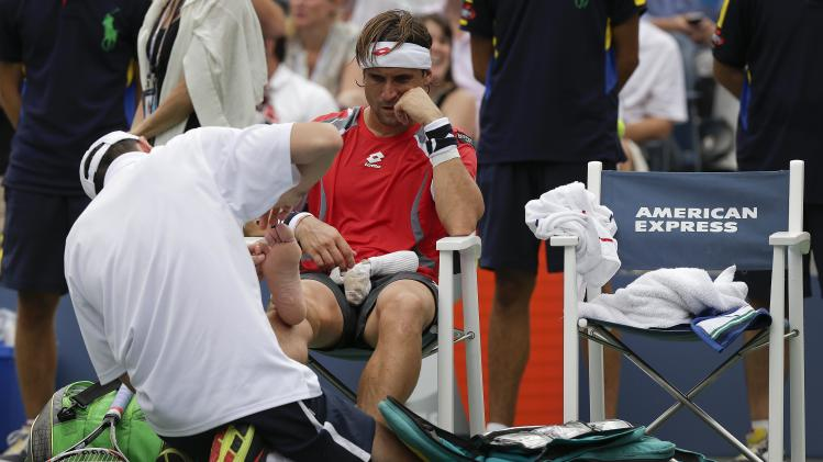 RETRANSMISSION FOR ALTERNATE CROP--Spain's David Ferrer has his right foot worked on during a medical timeout while playing Janko Tipsarevic of Serbia in the quarterfinals during the 2012 US Open tennis tournament,  Thursday, Sept. 6, 2012, in New York. (AP Photo/Peter Morgan)