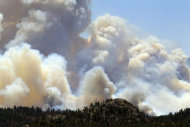 Smoke roils over a ridge east of Red Feather Lakes, Colo., on Sunday, June 17, 2012, as the High Park Fire continues to burn in northern Colorado. Crews are facing powerful winds as they battle the blaze that has scorched about 86 square miles of mountainous forest land and destroyed at least 181 homes, the most in state history. (AP Photo/David Zalubowski)