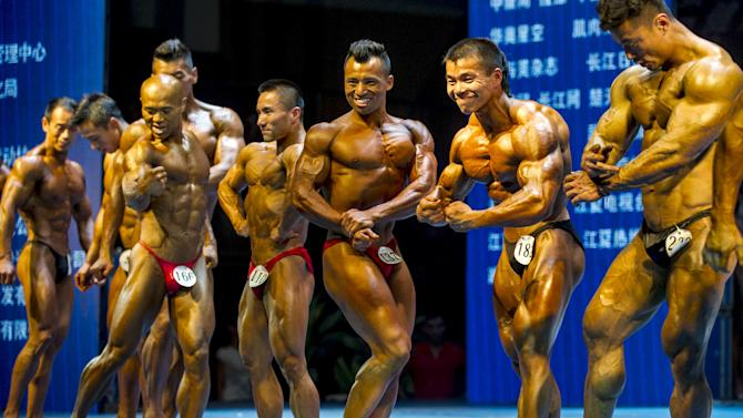 Participants compete during a bodybuilding contest at a gymnasium in Wuhan
