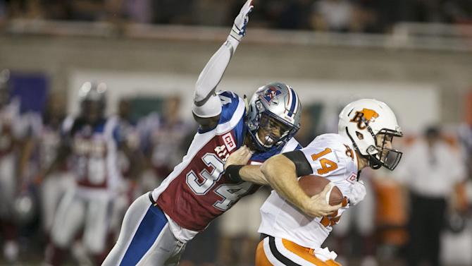 B.C. Lions quarterback Lulay is tackled by Montreal Alouettes' Hebert during their CFL football game in Montreal