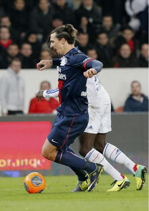 Paris Saint Germain's Zlatan Ibrahimovic of Sweden, front, vies for the ball with Lyon's Bakary Kone during their French League One soccer match, Sunday Dec. 1, 2013, in Parc des Princes stadium, in P