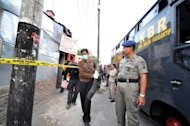 Indonesian anti-terror police secure a terror suspect's house during a raid in Mojosongo, Solo in central Java on October 27, 2012. Indonesian police arrested eleven suspected terrorists allegedly planning attacks on the US embassy and an American consulate, a spokesman said