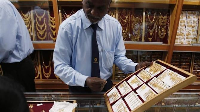Customers choose gold earrings at a jewellery shop in Kuala Lumpur