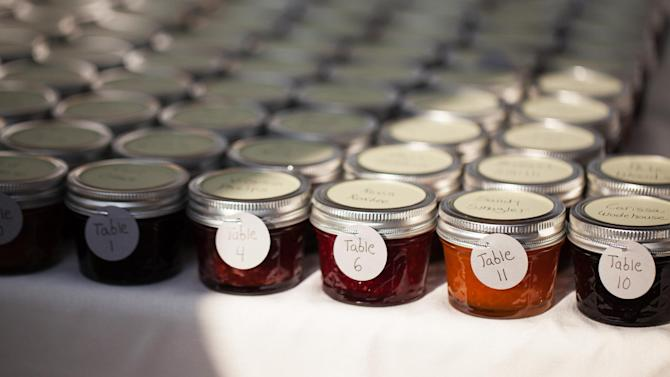 This Aug. 2, 2013 photo provided by Super9Studios.com shows homemade jam favors made by Jillian Simms for the guests at wedding of Jillian and Jason Simms. The wedding favor, that little thank-you-for-coming gift, has risen to new heights with the bride and groom giving guests a wide range of favors that are meaningful to them. (AP Photo Super9Studios.com, Irene Liebler)