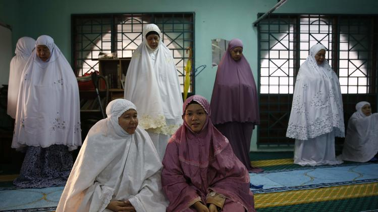 Muslim women wait to begin a prayer session on Eid al-Fitr in Kuala Lumpur
