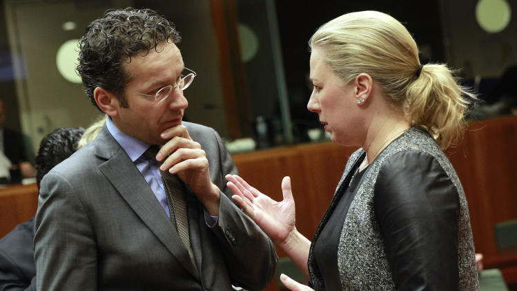 Finnish Finance Minister Jutta Urpilainen, right, talks with Dutch Finance Minister Jeroen Dijsselbloem prior to the start of the EU finance ministers meeting at the European Council building in Brussels, Tuesday, Feb. 18, 2014. (AP Photo/Yves Logghe)