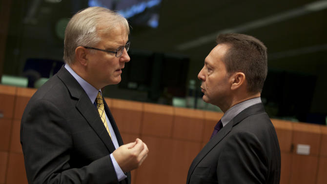 European Commissioner for the Economy Olli Rehn, left, speaks with Greek Finance Minister Yannis Stournaras during a meeting of eurogroup finance ministers in Brussels on Tuesday, Nov. 20, 2012. European Union officials will make a fresh try Tuesday to reaching a political accord on desperately needed bailout loans to Greece, an agreement that eluded them last week. (AP Photo/Virginia Mayo)