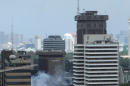 Smoke billows from an explosion in Jakarta, Indonesia, Thursday, Jan. 14, 2016. Suicide bombers exploded themselves in downtown Jakarta on Thursday while gunmen attacked a police post nearby, a witness told The Associated Press. Local television reported more explosions in other parts of the city. (Christian Hubel via AP) MANDATORY CREDIT