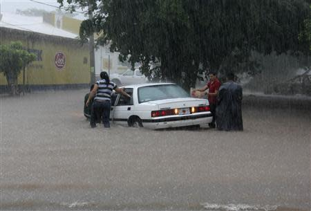 People try to get a car out of a flooded street in Culiacan