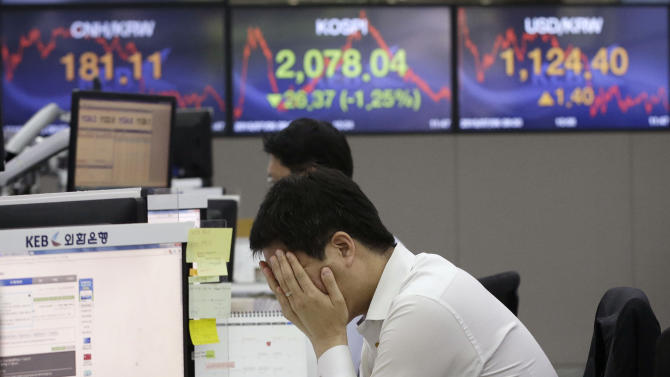 A currency trader covers his face with his hands at the foreign exchange dealing room of the Korea Exchange Bank headquarters in Seoul, South Korea, Monday, July 6, 2015. Asian markets mostly fell Monday as investors reacted to Greece's sound rejection of terms set by its international creditors, deepening uncertainties over its status as a member of the 19-nation eurozone. (AP Photo/Ahn Young-joon)