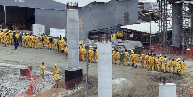 Labourers line up at the site of expansion works for the international airport in Guarulhos