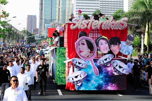 "The cast of the MMFF 2012 entry ""Sisterekas"" waves to the crowd as their float makes its way at the 2012 Metro Manila Film Festival Parade of Stars on 23 December 2012. (Angela Galia/NPPA Images)"