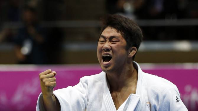 South Korea's Lee celebrates after defeating Kazakhstan's Bolat in their men's team gold medal judo contest at Dowon Gymnasium during the 17th Asian Games in Incheon