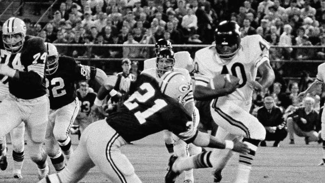 FILE - This Aug. 18, 1967, file photo shows Gale Sayers (40) of the Chicago Bears grinding out yardage against the Green Bay Packers before being brought down by Bob Jeter (21) at the Midwest Shrine exhibition game in Milwaukee. The Bears and Packers have played 181 times, with Chicago holding a 92-83-6 edge. Between them, they've won 21 NFL titles and sent four dozen players to the Hall of Fame.  (AP Photo/File)