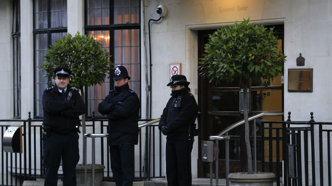 British police officers stand guard outside the King Edward VII hospital in London where Queen Elizabeth II has admitted to be assessed for symptoms of gastroenteritis, Sunday, March 3, 2013. (AP Photo/Sang Tan)