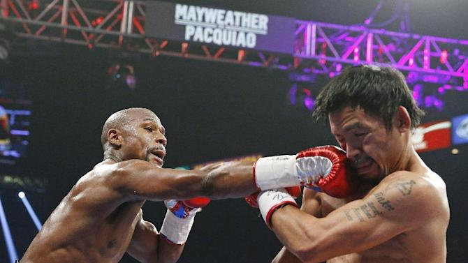 Floyd Mayweather Jr., left, connects with a right to the head of Manny Pacquiao, from the Philippines, during their welterweight title fight on Saturday, May 2, 2015 in Las Vegas. (AP Photo/John Locher)