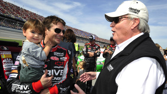 Jeff Gordon holds his son, Leo, and speaks with team owner Rick Hendrick before the NASCAR Sprint Cup Series auto race at Talladega Superspeedway on Sunday, Oct. 23, 2011, in Talladega, Ala. (AP Photo/Rainier Ehrhardt)