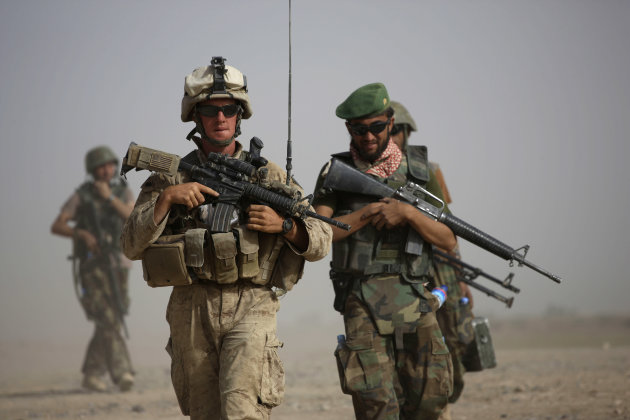 FILE - In this  Oct. 3, 2009 file photo, U.S. Marine squad leader Sgt. Matthew Duquette, left, of Warrenville, Ill., with Bravo Company, 1st Battalion 5th Marines walks with Afghan National Army Lt. H