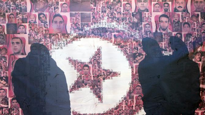 Tunisians are silhouetted behind a poster showing victims' portraits of the Revolution, in Tunis, Sunday, Jan. 13, 2013 as the country prepares to celebrate the second anniversary of the Revolution. Two years after the revolution that overthrew an authoritarian president and started the Arab Spring, Tunisia is struggling with high unemployment and rising violence in its politics. (AP Photo/Amine Landoulsi)