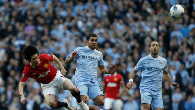 Manchester City's Vincent Kompany, bottom, competes for the ball with Manchester United's Park Ji-Sung, left, during the English Premier League soccer match between Manchester City and Manchester United at the Etihad Stadium in Manchester, Monday, April 30, 2012.  (AP Photo/Matt Dunham)