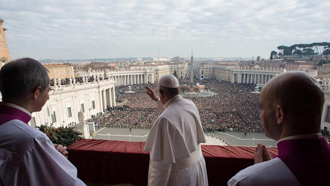 "Pope Francis waves as he delivers a ""Urbi et Orbi"" (to the city and world) message from the balcony overlooking St. Peter's Square at the Vatican"