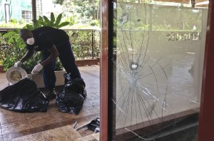 A man cleans up next to the bullet-scarred window of …