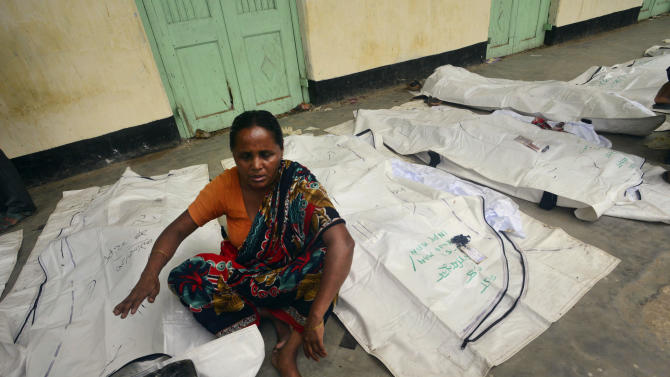 A Bangladeshi woman, in between a line of dead bodies, closes her eyes as she tries to identify a body, at a school turned make-shift morgue for victims of the garment factory building collapse in Savar near Dhaka, Bangladesh, Friday, May 10, 2013. The death toll from a garment factory building that collapsed more than two weeks ago near the Bangladeshi capital soared past 1,000 on Friday, with no end in sight to the stream of bodies being pulled from the wreckage of the worst-ever garment industry disaster. (AP Photo/Ismail Ferdous)