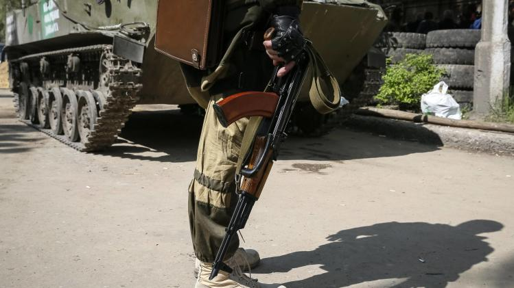 A pro-Russian armed man holds on to his weapon as he stands guard near the state security service building in Slaviansk