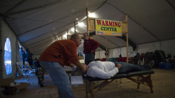 A free massage is given in a warming center tent in the Rockaways, Saturday, Nov. 10, 2012, in the Queens borough of New York. Despite power returning to many neighborhoods in the metropolitan area after Superstorm Sandy crashed into the Eastern Seaboard, many residents of the Rockaways continue to live without power and heat due to damage caused by Sandy. (AP Photo/John Minchillo)
