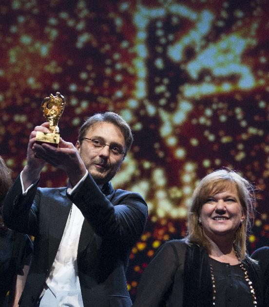 Director Calin Peter Netzer holds the Golden Bear for his film Child's Pose alongside producer Ada Solomon at the closing ceremony at the 63rd edition of the Berlinale, International Film Festival in Berlin, Saturday, Feb. 16, 2013. (AP Photo/Gero Breloer)