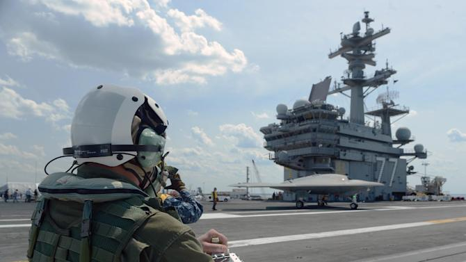In this image provided by the U.S. Navy, Dave Lorenz, a Northrop Grumman deck operator, drives an X-47B Unmanned Combat Air System demonstrator using an arm-mounted controller on the flight deck of the aircraft carrier USS George H.W. Bush Friday May 10, 2013. The George H.W. Bush is scheduled to be the first aircraft carrier to catapult launch an unmanned aircraft from its flight deck Tuesday May 14, 2013. (AP Photo/US Navy, Specialist 2nd Class Timothy Walter)