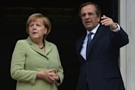 <p>Greek Prime Minister Antonis Samaras (R) welcomes German Chancellor Angela Merkel in Athens. Police fired tear gas to disperse protesters attempting to storm a barricade near parliament as tens of thousands massed in a show of anger against Merkel.</p>