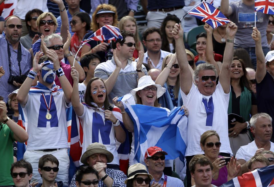 Fans of Andy Murray of Great Britain cheer during his match against Roger Federer of Switzerland during the gold medal men's singles at the All England Lawn Tennis Club in Wimbledon, London at the 2012 Summer Olympics, Sunday, Aug. 5, 2012. (AP Photo/Elise Amendola)