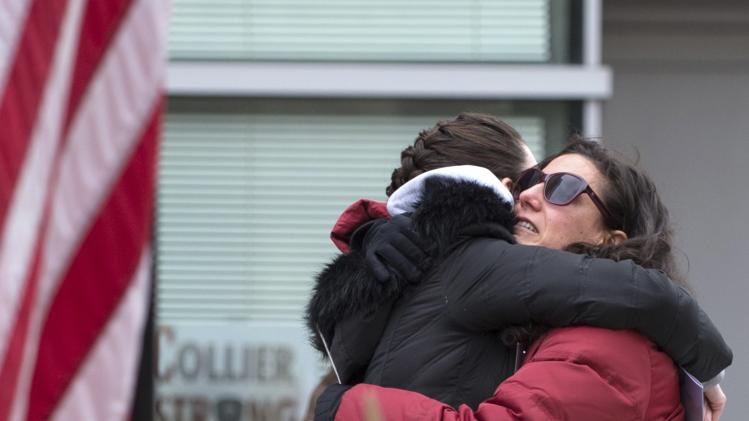 Shafran hugs Earls near a makeshift memorial for Collier in Cambridge