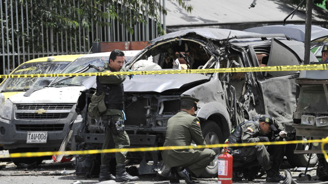 Police inspect the scene after a bomb exploded in Bogota, Colombia, Tuesday, May 15, 2012. A bomb targeting former Colombian interior minister Fernando Londono killed two of his bodyguards and injured at least 31 others in the heart of Bogota's uptown commercial district, authorities said.  (AP Photo/Carlos Julio Martinez)