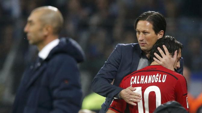 Bayer Leverkusen's coach Schmidt hugs substituted Calhanoglu during their German first division Bundesliga soccer match against Schalke 04 in Leverkusen
