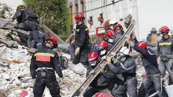 """French firemen search in the rubble of a building after an explosion collapsed it, in Rosny-sous-Bois, outside Paris, Sunday, Aug. 31, 2014. French authorities say a four-story building in a northeastern Paris suburb has collapsed after an explosion, killing a child. More people are thought to underneath the rubble. Speaking on i-Tele, fire department spokesman Gabriel Plus said around 10 people were evacuated from the building in Rosny-sous-bois that occurred early Sunday morning. Plus said that around another 10 people could still be underneath the rubble, and emergency teams were working hard to rescue people who might be trapped. """"We could still find living victims in the hours to come,"""" he said. Interior Minister Bernard Cazeneuve has arrived at the scene, but couldn't confirm a theory that the explosion was caused by a gas leak. (AP Photo/Christophe Ena)"""