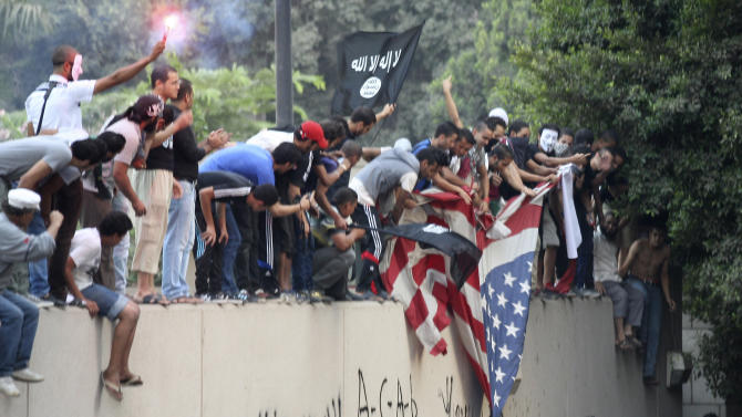 Protesters destroy an American flag pulled down from the U.S. embassy in Cairo, Egypt, Tuesday, Sept. 11, 2012. Egyptian protesters, largely ultra conservative Islamists, have climbed the walls of the U.S. embassy in Cairo, went into the courtyard and brought down the flag, replacing it with a black flag with Islamic inscription, in protest of a film deemed offensive of Islam. (AP Photo/Mohammed Abu Zaid)