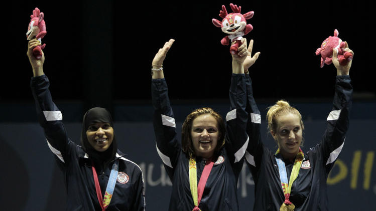 The United States women fencing team, from left, Ibtihaj Muhammad, Dagmara Wozniak and Mariel Zagunis celebrate in the podium after winning the gold medal in the sabre team event at the Pan American Games in Guadalajara, Mexico, Friday, Oct. 28, 2011. (AP Photo/Jorge Saenz)